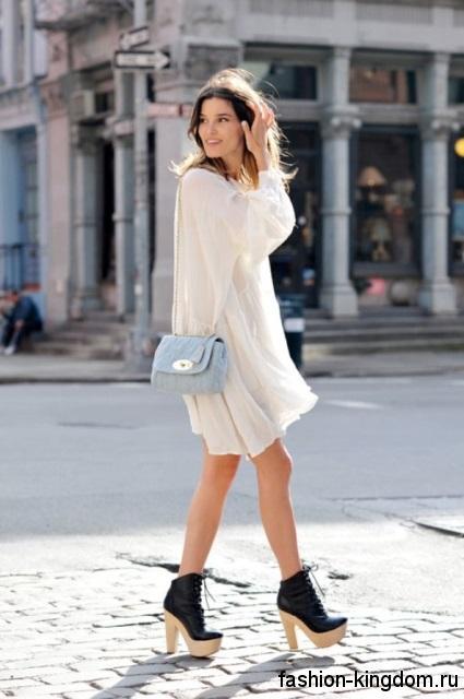 Летняя женская сумочка голубого цвета дополнит белое платье свободного силуэта и ботильоны черного тона.