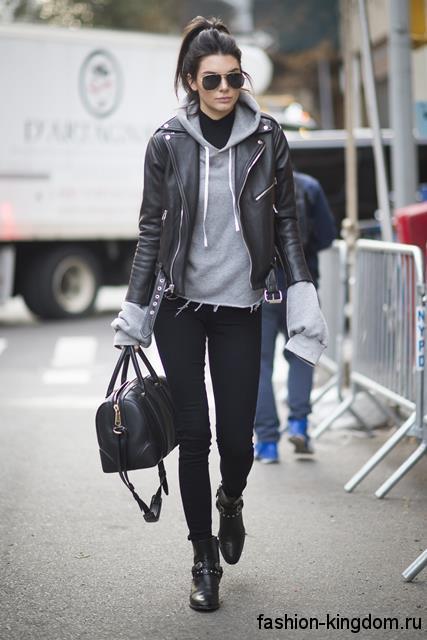 Кожаная куртка в стиле кэжуал сочетается с серой кофтой, узкими черными брюками и кожаными ботинками.