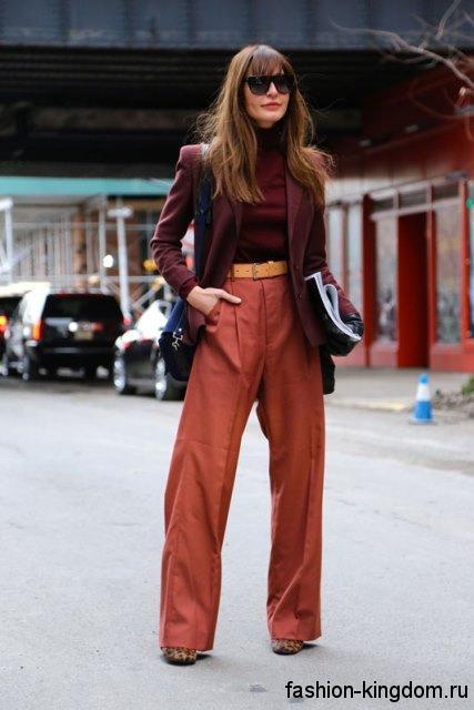 Классические брюки терракотового цвета, свободного силуэта, с желтым поясом сочетаются с блузкой и пиджаком бордового тона.