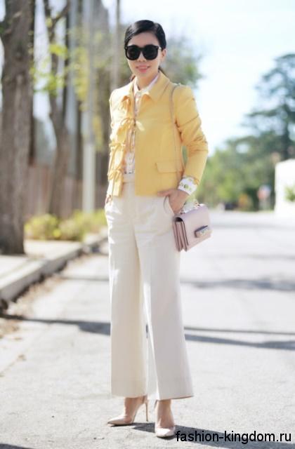 Прямые классические брюки белого цвета, расширенного кроя гармонируют с коротким желтым жакетом.