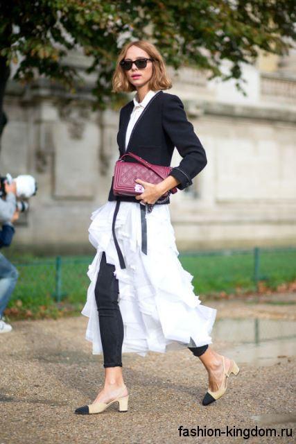 Открытые модные туфли черно-бежевого тона на низком каблуке сочетаются с белой юбкой и черным жакетом.