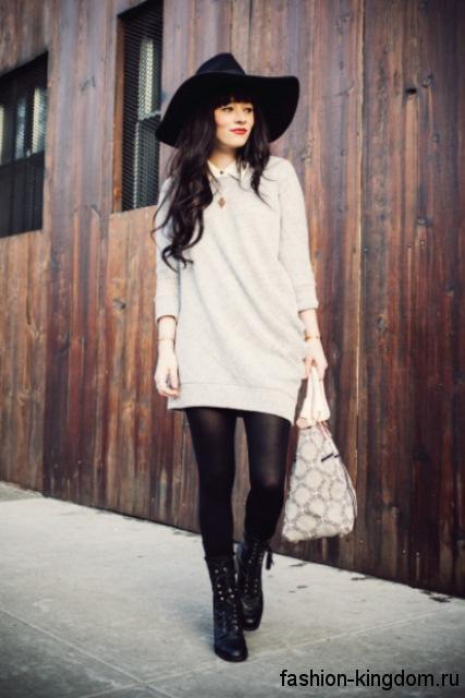 Осенняя туника молочного тона, свободного кроя в стиле кэжуал гармонирует с черной шляпой и белой сумочкой.