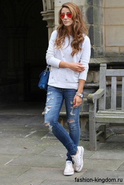 Рваные джинсы синего цвета в стиле кэжуал в сочетании с белой кофтой свободного фасона и белыми кедами.