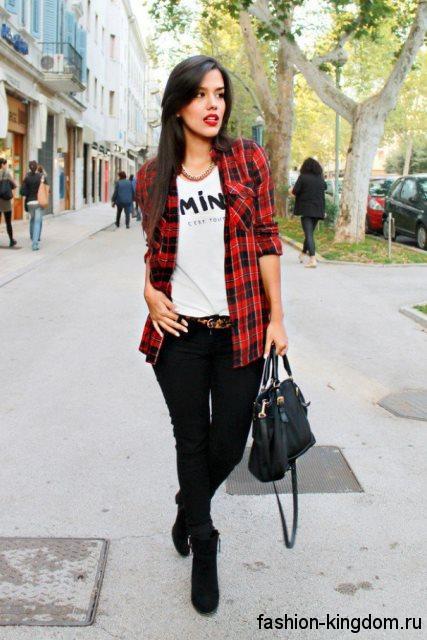 Рубашка в клетку красно-черного цвета, свободного фасона в стиле кэжуал сочетается с узкими черными брюками.