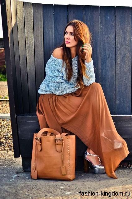 Большая летняя женская сумка рыжего тона, прямоугольной формы сочетается с длинной коричневой юбкой и серебристыми туфлями.