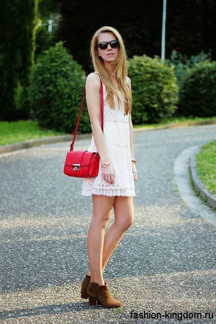 Красная летняя женская сумочка прямоугольной формы, на длинном ремешке в тандеме с ажурным белым платьем и коричневыми ботильонами на каблуке.