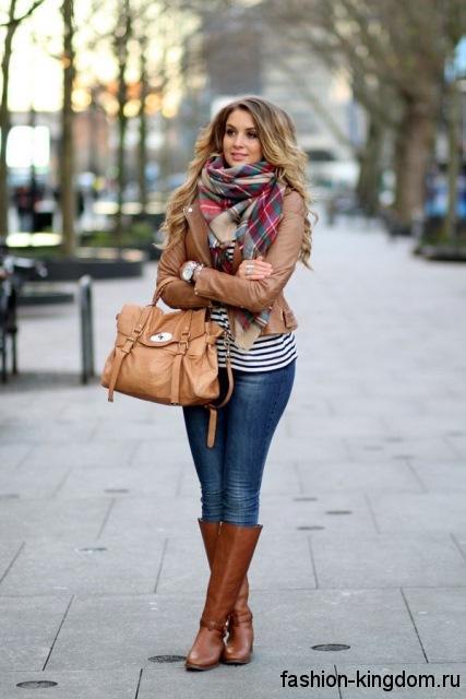 Синие джинсы в стиле кэжуал сочетаются с кожаной курткой коричневого цвета и высокими сапогами рыжего тона.