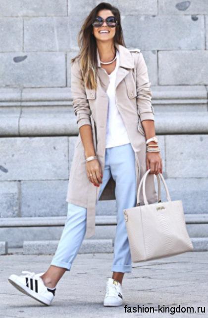 Укороченные голубые джинсы прямого кроя в стиле кэжуал сочетаются с плащом бежевого цвета, белым кедами и сумочкой молочного тона.
