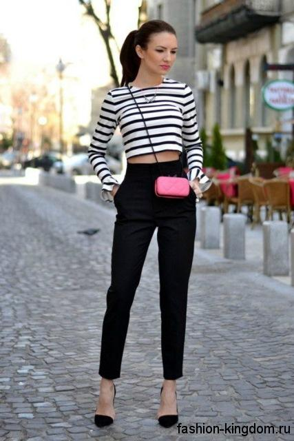 Укороченные классические брюки черного цвета, прямого кроя гармонируют с короткой кофточкой черно-белого тона в полоску и черными туфлями на каблуке.
