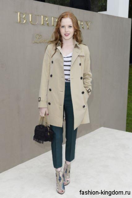 Короткие классические брюки темно-зеленого цвета сочетаются с двубортным бежевым пальто и ботильонами на каблуке.