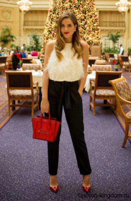Укороченные классические брюки черного цвета в сочетании с белой блузкой без рукавов, сумочкой и туфлями красного тона.