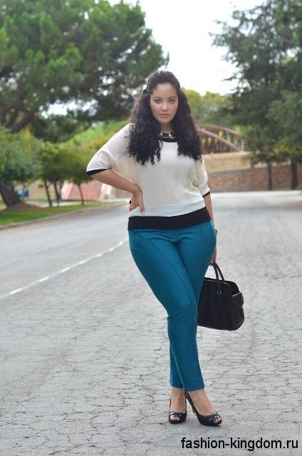 Узкие классические брюки бирюзового цвета для полных девушек сочетаются с белой блузкой и открытыми туфлями на каблуке.