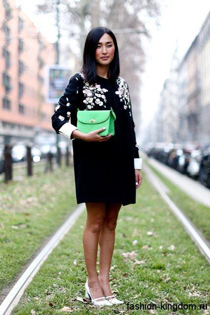 Модные бежевые туфли на широком низком каблуке дополняют короткое черное платье с белой вышивкой и рукавами три четверти.