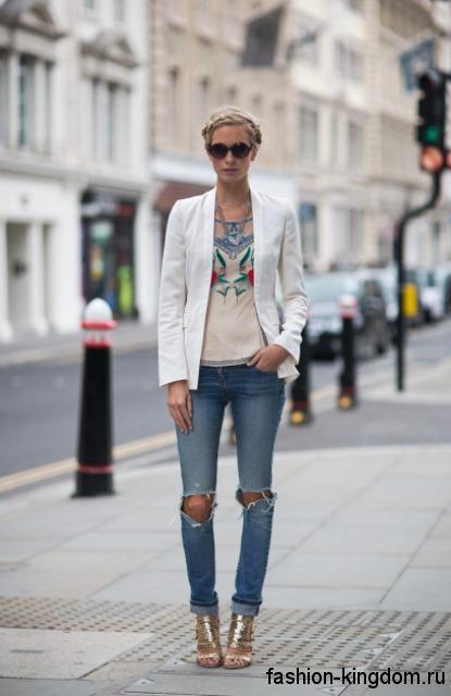 Рваные синие джинсы в стиле кэжуал сочетаются с пиджаком белого цвета и золотистыми босоножками на каблуке.