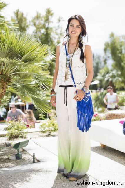 Женская летняя сумочка синего цвета, с бахромой, в стиле хиппи, на длинном ремешке в тандеме с брюками и жилеткой белого тона.