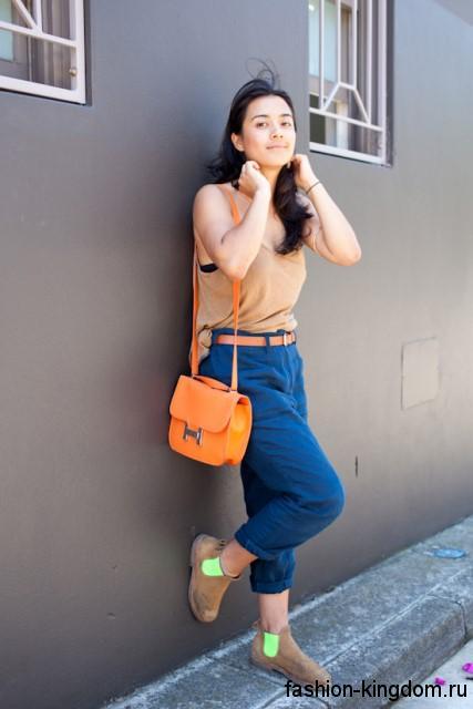 Ярко-оранжевая летняя женская сумочка на длинном ремешке сочетается с бежевым топом и синими джинсами.