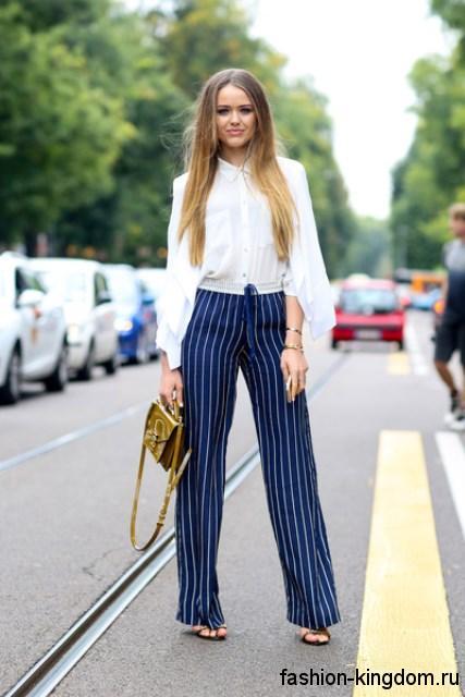 Прямые классические брюки синего цвета в белую вертикальную полоску в тандеме с белой блузкой и босоножками на каблуке.
