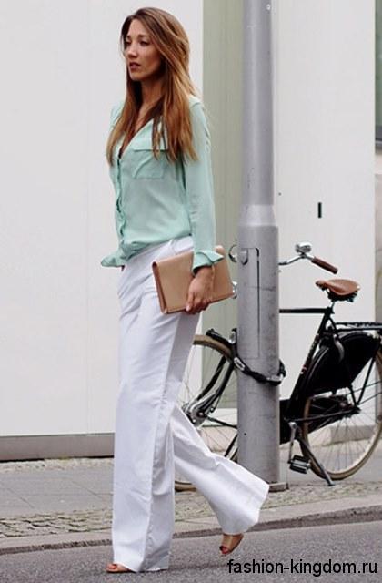 Классические белые брюки свободного кроя гармонируют с блузкой мятного оттенка с длинными рукавами.