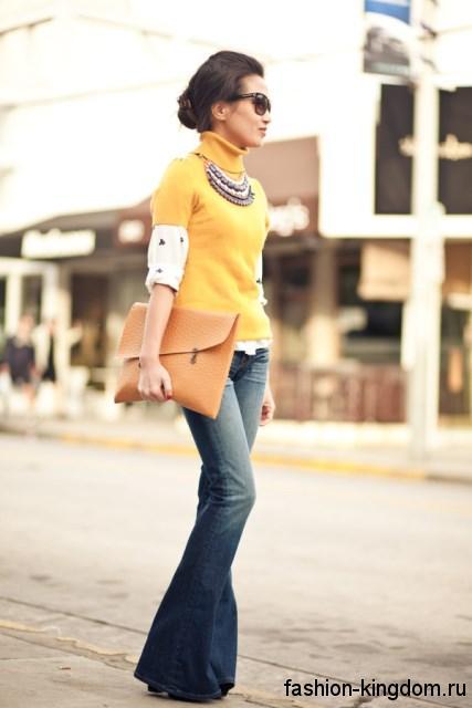Синие джинсы-клеш в стиле кэжуал сочетаются с желтой кофточкой и сумкой-конверт оранжевого тона.