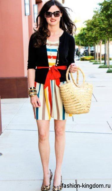 Плетеная летняя женская сумочка округлой формы гармонирует с коротким платьем в цветную полоску и туфлями с леопардовым принтом.