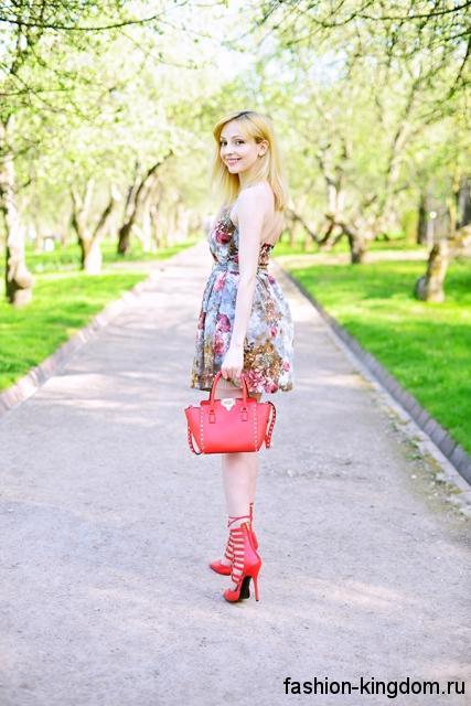 Красная женская летняя сумочка на коротких ручках сочетается с коротким платьем с цветочным рисунком и красными туфлями на каблуке.