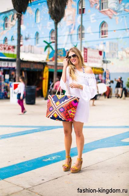 Разноцветная летняя женская сумочка сочетается с белым коротким платьем и желтыми босоножками на платформе.