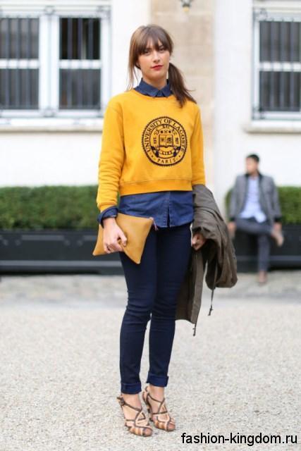 Короткая кофточка желтого цвета, прямого кроя в стиле кэжуал сочетается с узкими джинсами темно-синего оттенка.