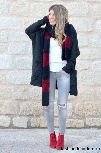 Серые рваные джинсы в стиле casual сочетаются с кардиганом черного цвета, свободного фасона, черно-красным шарфом.