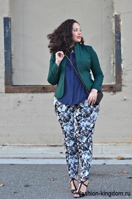Классические брюки серого тона с цветочным принтом для полных гармонируют с зеленым жакетом и босоножками на каблуке.