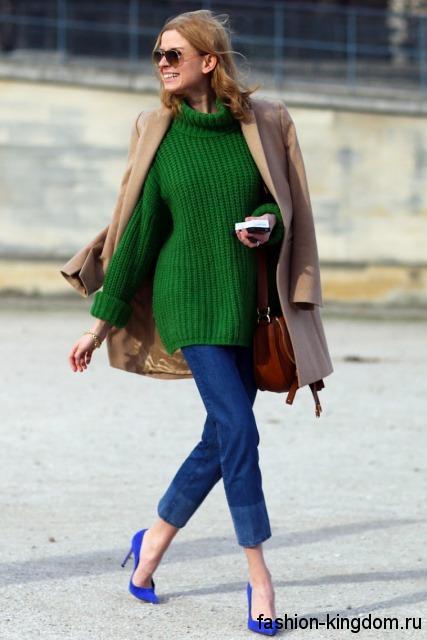 Синие модные туфли на шпильке гармонируют с джинсами синего тона, зеленым вязаным свитером и бежевым пальто выше колен.