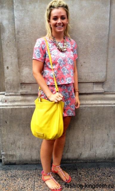 Ярко-желтая летняя женская сумка на длинном ремешке дополняет юбки и блузку розового тона и босоножки на плоской подошве.