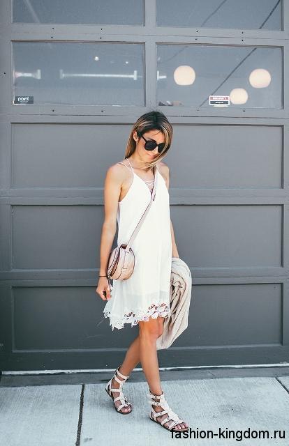 Круглая летняя сумочка бежевого цвета сочетается с коротким белым платьем и босоножками белого тона на плоской подошве.