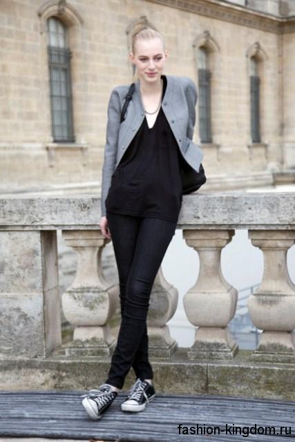 Узкие черные джинсы сочетаются с черной блузкой, жакетом серого цвета и кедами черно-белого тона.
