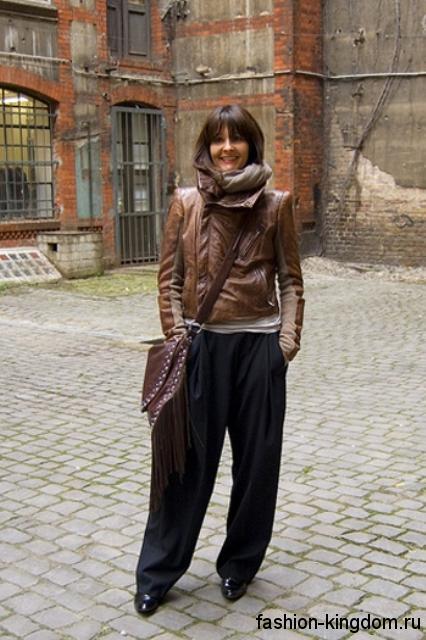 Кожаная коричневая куртка в стиле кэжуал сочетается с широкими брюками, кожаной сумкой и шарфом кофейного оттенка.