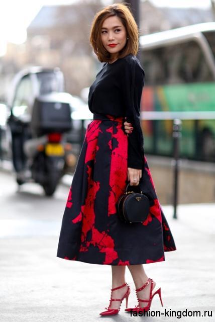 Открытые модные туфли красного цвета на шпильке в сочетании с пышной юбкой красно-черного тона и черной блузкой с длинными рукавами.