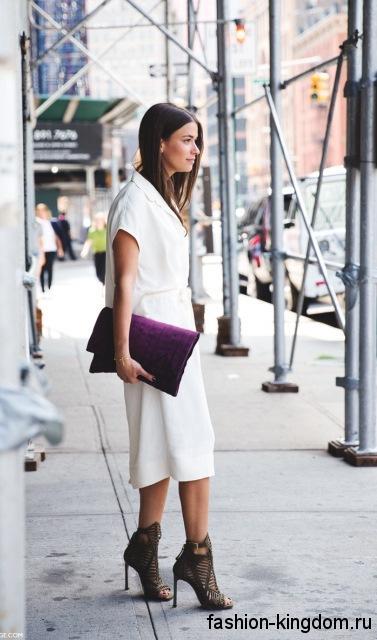 Летняя женская сумка клатч темно-фиолетового цвета сочетается с белым платьем-миди, свободного силуэта.