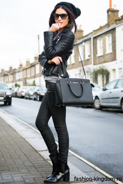 Кожаная черная куртка в стиле кэжуал гармонирует с узкими черными брюками аксессуарами и ботинками черного цвета.