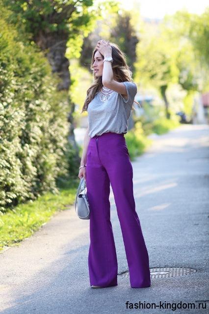 Классические брюки фиолетового тона гармонируют с серой блузкой с короткими рукавами.