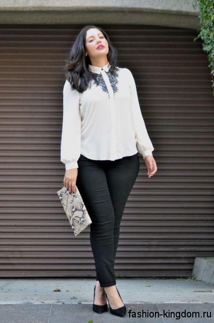 Узкие классические брюки черного цвета сочетаются с белой блузкой и черными туфлями на высоком каблуке.