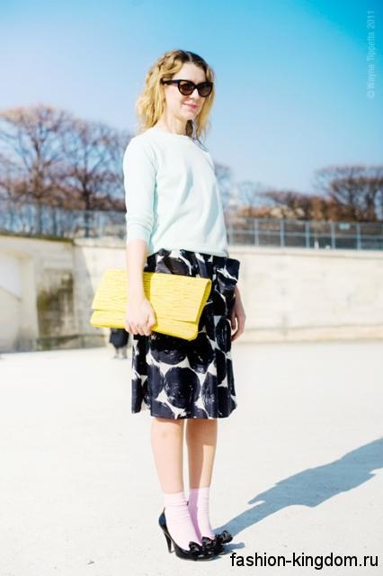 Модные туфли на низком каблуке черного тона с бантиком в тандеме с юбкой-миди, кофточкой и желтой сумкой.
