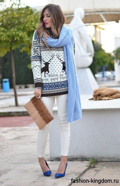 Вязаный свитер с рисунком дополняет модный стиль кэжуал, сочетаясь с белыми брюками и голубым шарфом.