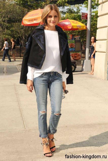 Рваные джинсы светло-голубого цвета в стиле кэжуал в сочетании с белой кофтой и коротким черным жакетом.