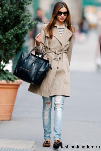 Узкие рваные джинсы голубого цвета сочетаются с демисезонным бежевым пальто и большой кожаной сумкой.