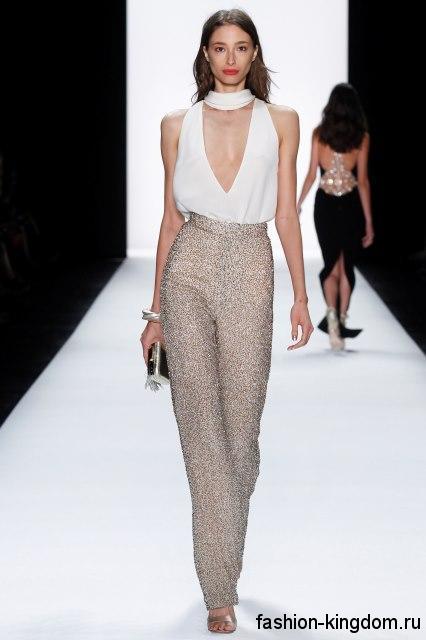 Вечерние классические брюки бежевого тона из блестящей ткани, с высокой талией в тандеме с открытой белой блузкой от Badgley Mischka.