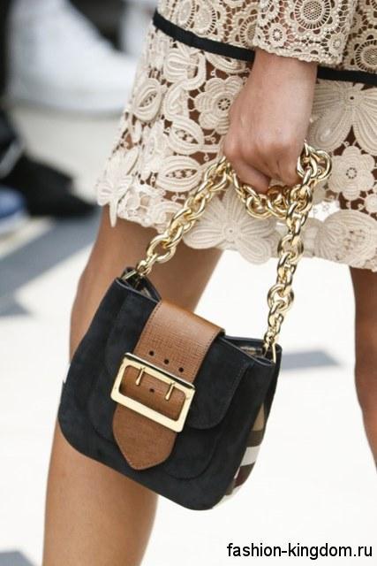 Маленькая летняя женская сумочка округлой формы, черного цвета, с коричневой вставкой и на цепочке от Burberry Prorsum.