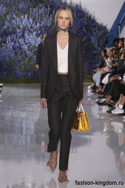 Черные классические брюки прямого кроя в сочетании с черным пиджаком и бежевыми туфлями на каблуке от Dior.