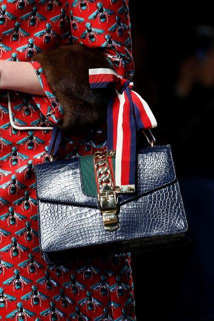 Небольшая летняя женская сумочка темно-синего цвета, с металлическими вставками и небольшой ручкой от Gucci.