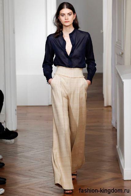 Классические широкие брюки бежевого цвета с высокой талией в тандеме с шифоновой темно-синей блузкой от Martin Grant.