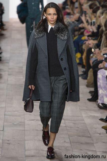 Короткая модель классических брюк серого цвета в клетку в тандеме с серым пальто-кейп и лакированными туфлями от Michael Kors.