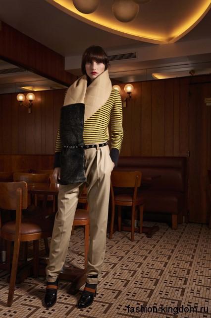 Атласные классические брюки бежевого цвета, зауженного кроя сочетаются с желтой полосатой кофточкой и черными ботильонами на каблуке от Sonia Rykiel.